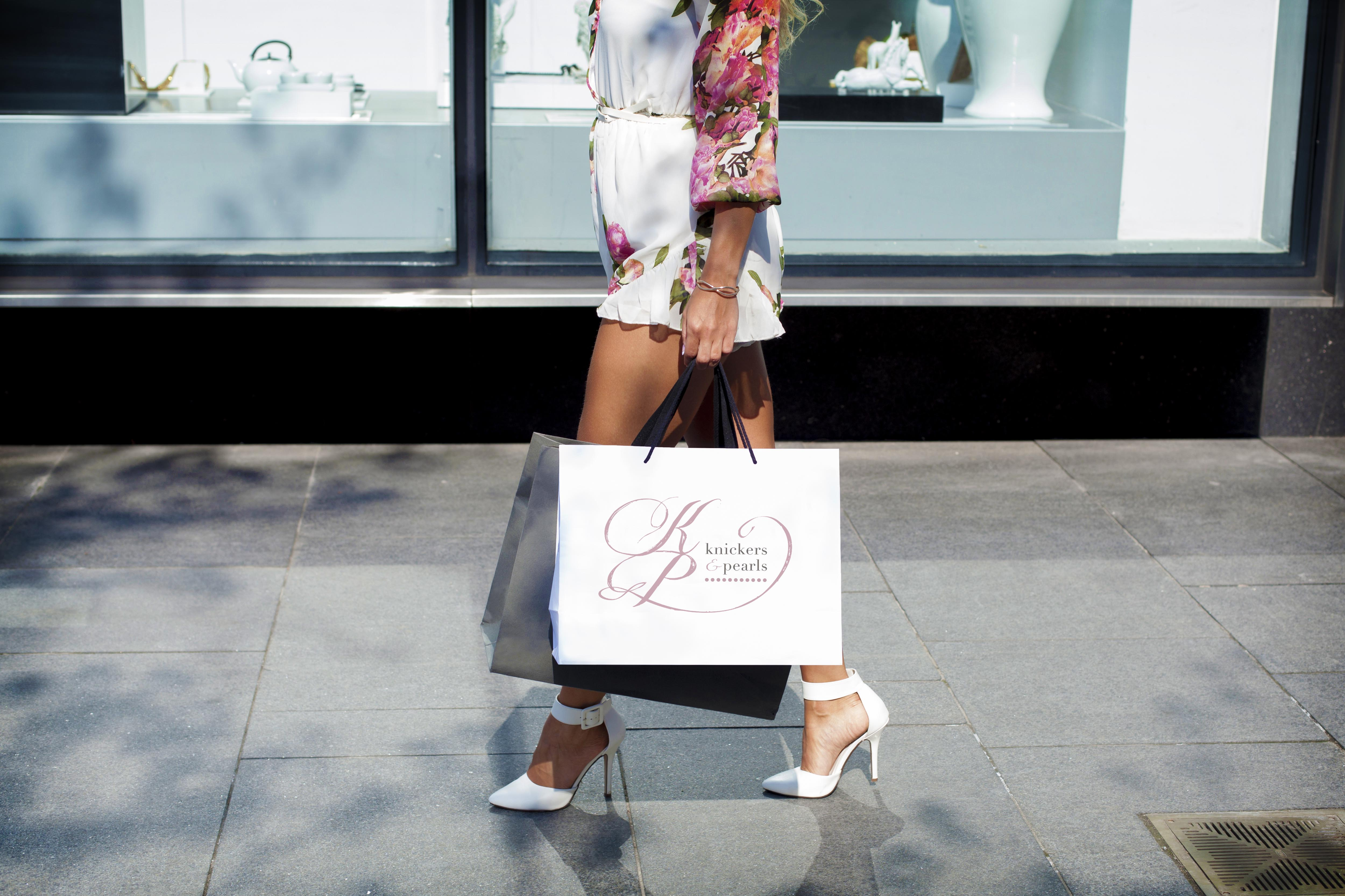 logo design for Knickers and Pearls on a white shopping bag held by a fashionable woman in Yountville, California