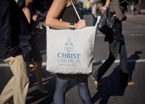 logo design for Christ Church Macon shown on a white tote bag held by a young woman