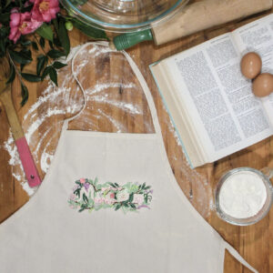 Macon Floral design stitched onto a plain canvas apron with cookbook and baking supplies, Macon gift or souvenir