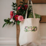 Macon Floral design embroidered on a tote bag hanging from a hook with flowers and a book inside, Macon gift or souvenir for family or visitors