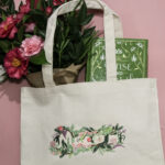 Macon Floral design embroidered on a tote bag on a pink background with flowers and a book inside