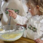 image of toddler girl wearing a custom 'Macon Floral' aprons while baking with her mom