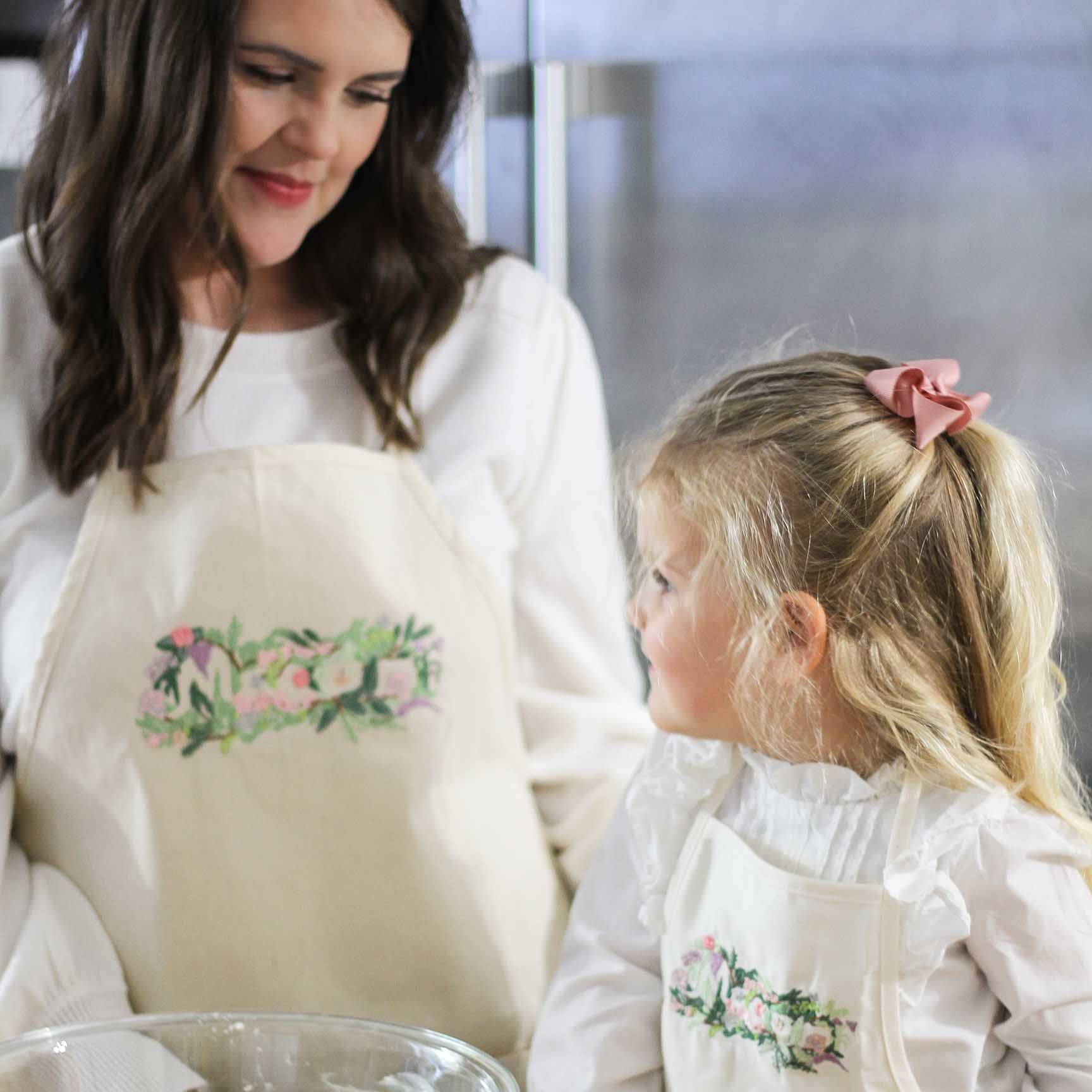 image of mother and daughter wearing matching aprons while baking, embroidered with 'Macon Floral Design'